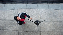 Photograph of a top-down reflection of a photographer triggering a camera on a tripod using a remote control.