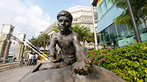 Photograph of the statue of an Indian coolie loading goods onto a bullock cart, which is part of a bronze sculpture series, The River Merchants by Aw Tee Hong, at Boat Quay, Singapore.